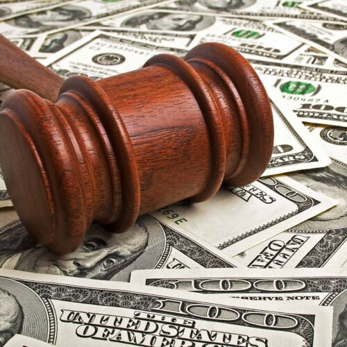 Photo of gavel laying on money