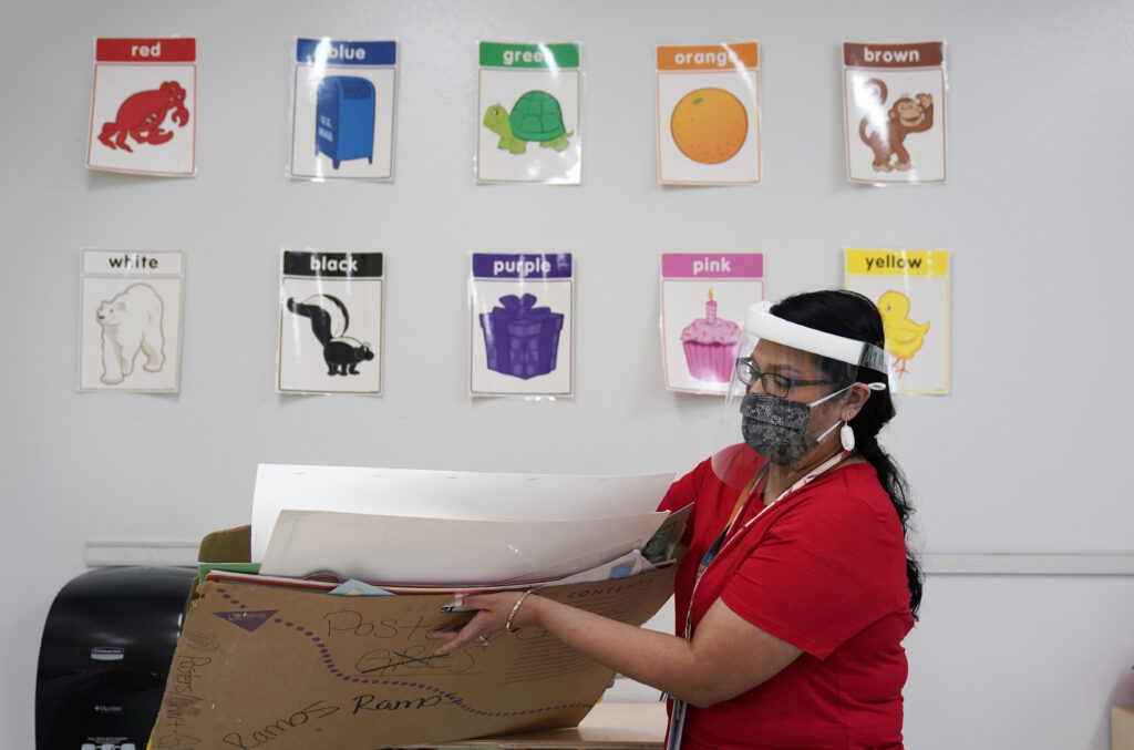 Teacher Judith Ramos wears a face mask as she prepares her classroom. The ADA requires workplaces to make reasonable arrangements that will allow workers with disabilities to do their jobs.