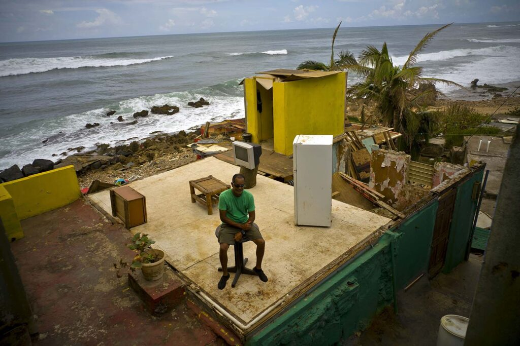 Roberto Figueroa Caballero sits on a small table in his home in Puerto Rico destroyed by Hurricane Maria.