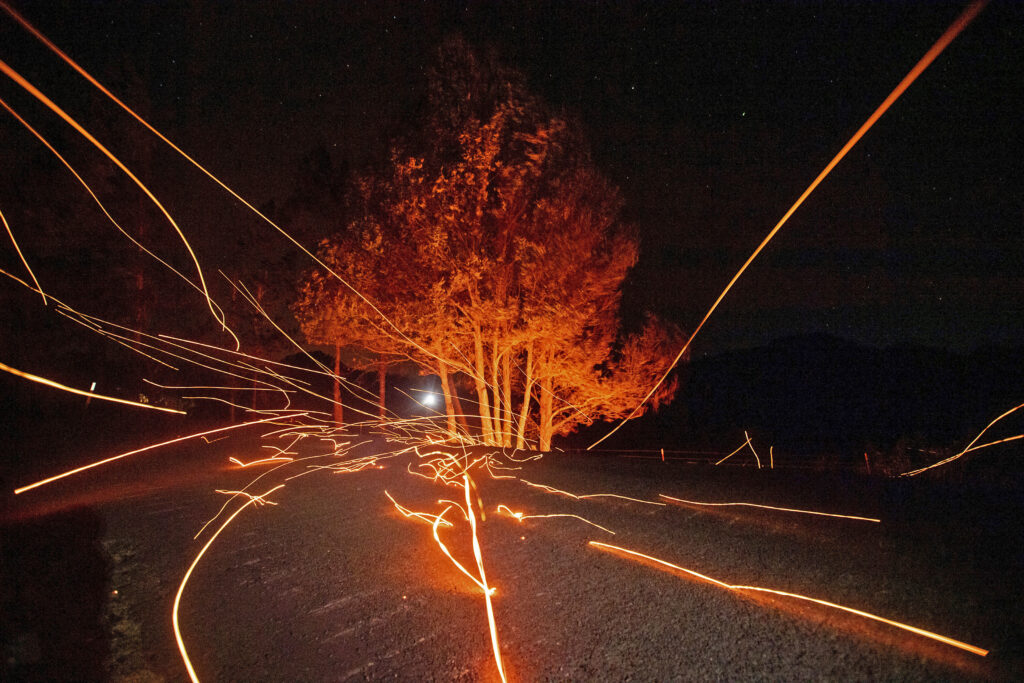Strong winds send embers flying from a tree.