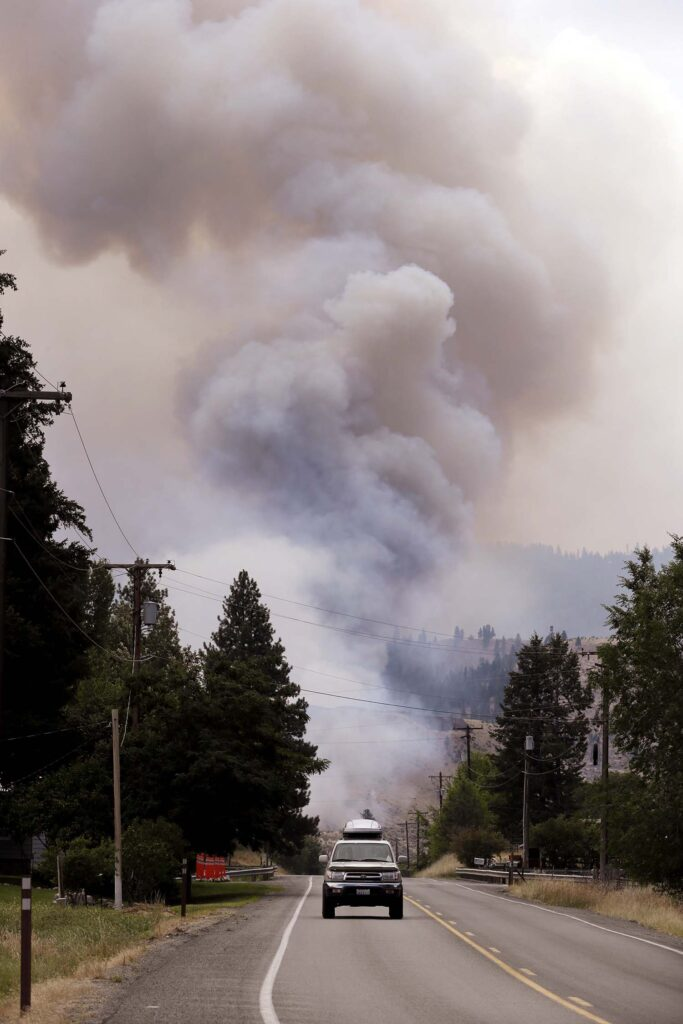 Smoke rises in the distance near Carlton, Washington. A wildfire in rural north-central Washington destroyed homes.