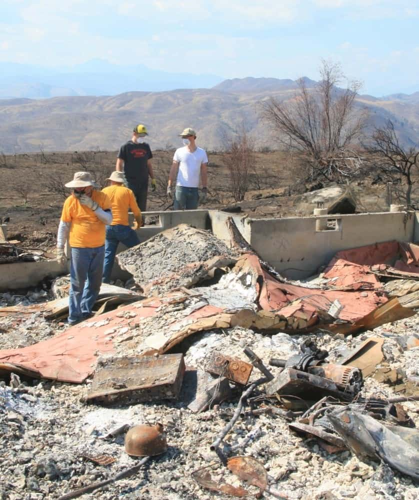 A crew of Southern Baptists from California looks for items that survived one of the wildfires in the Methow Valley, hoping to give homeowners some closure.