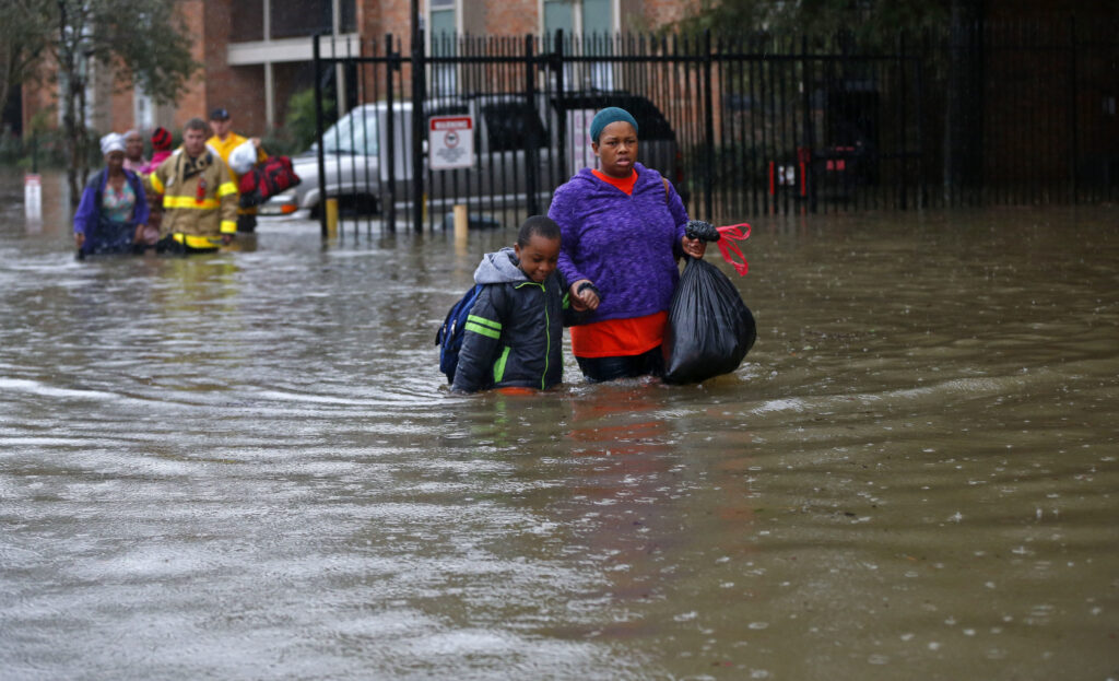Residents wade through floodwaters from heavy rains in Baton Rouge in 2016. There were polling place changes in 2016, which added to the confusion of after the floods.