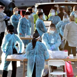 Medical personnel prepare to test hundreds of people lined up in vehicles in Phoenix's western neighborhood for free COVID-19 tests.