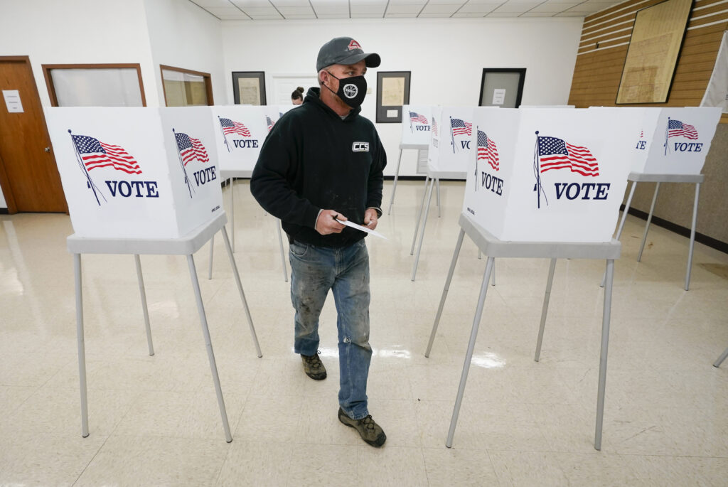 Chris Helps, of Earlham, Iowa, makes his way to the ballot box at a polling place during early voting.