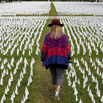 Artist Suzanne Brennan Firstenberg walks among thousands of white flags planted in remembrance of Americans who have died of COVID-19.