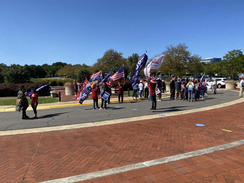 Supporters of President Donald Trump raise banners at a polling place in Virginia. Some called it voter intimidation.