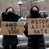 Protestors hold signs at the End The Violence Towards Asians rally in New York City.