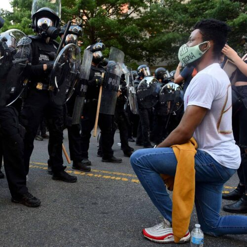 A protester kneels in front of a row of police.