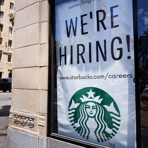 A 'We're Hiring!' sign is displayed at a Starbucks. Wages rose across all racial groups in the first 3 months of 2021.