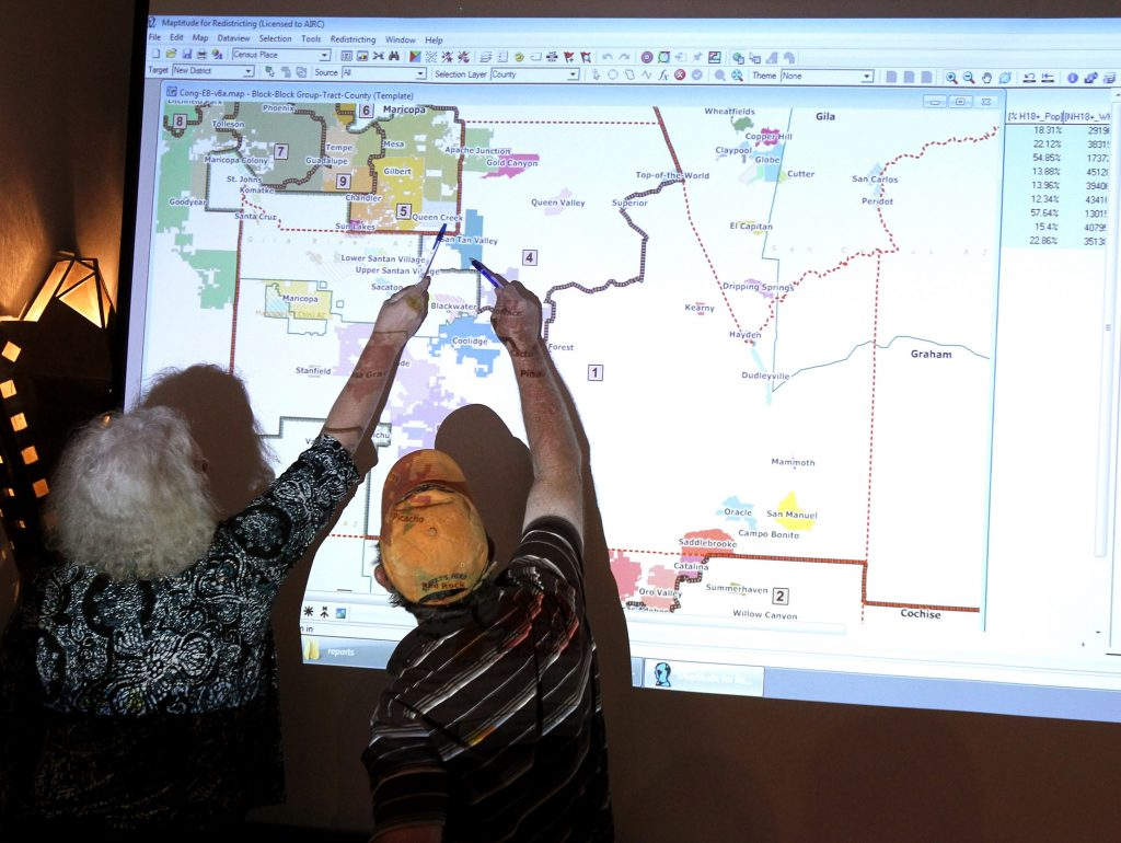 Commission attorney Mary O'Grady speaks with a Casa Grande city council member as they point to a possible map outlining the new congressional landscape during an Arizona redistricting meeting.