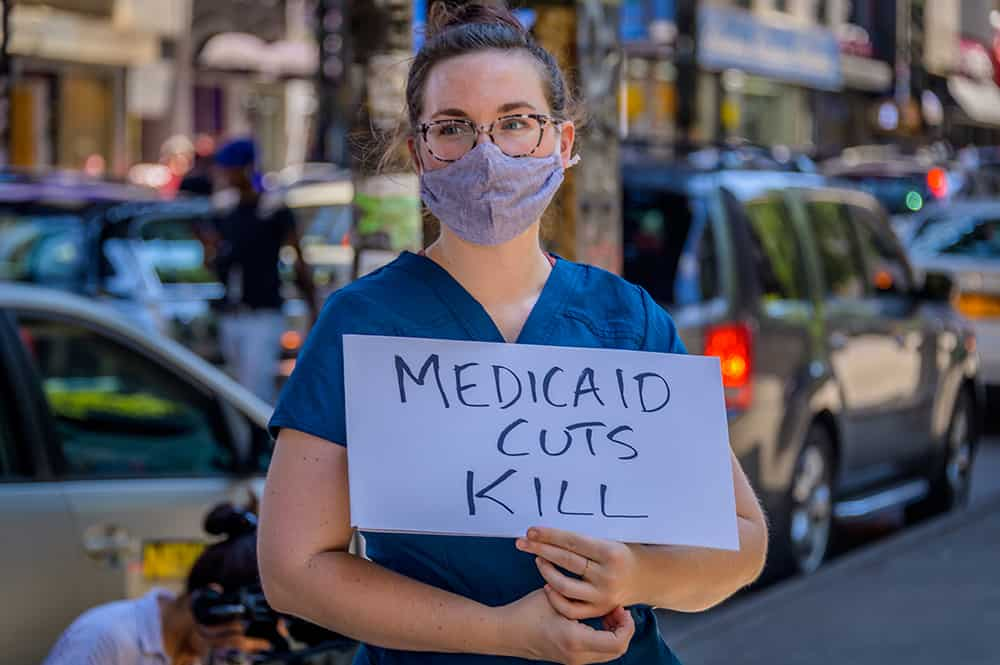"""A participant holds a """"Medicaid Cuts Kill"""" sign at a rally to demand justice for Sha-Asia Washington, a 26-year-old Black New Yorker, who died on July 3, 2020, during childbirth at a the Brooklyn hospital."""