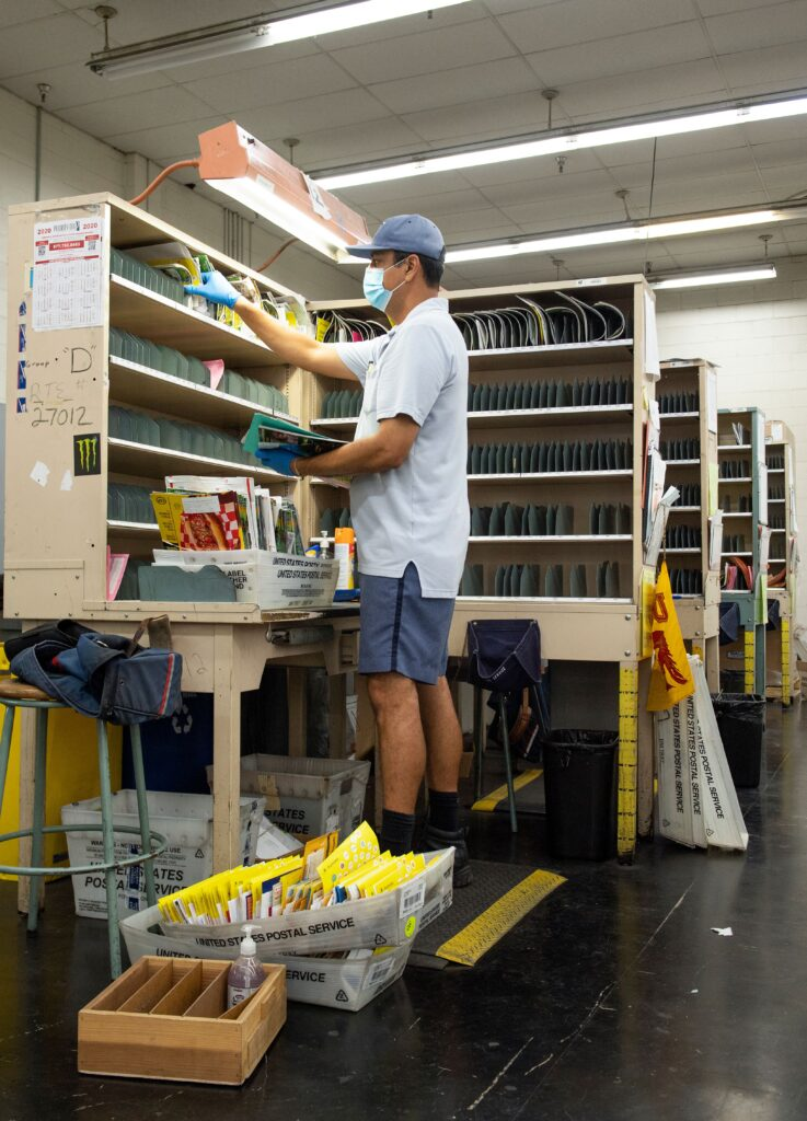 Mail carrier Oscar Osorio sorts the mail.
