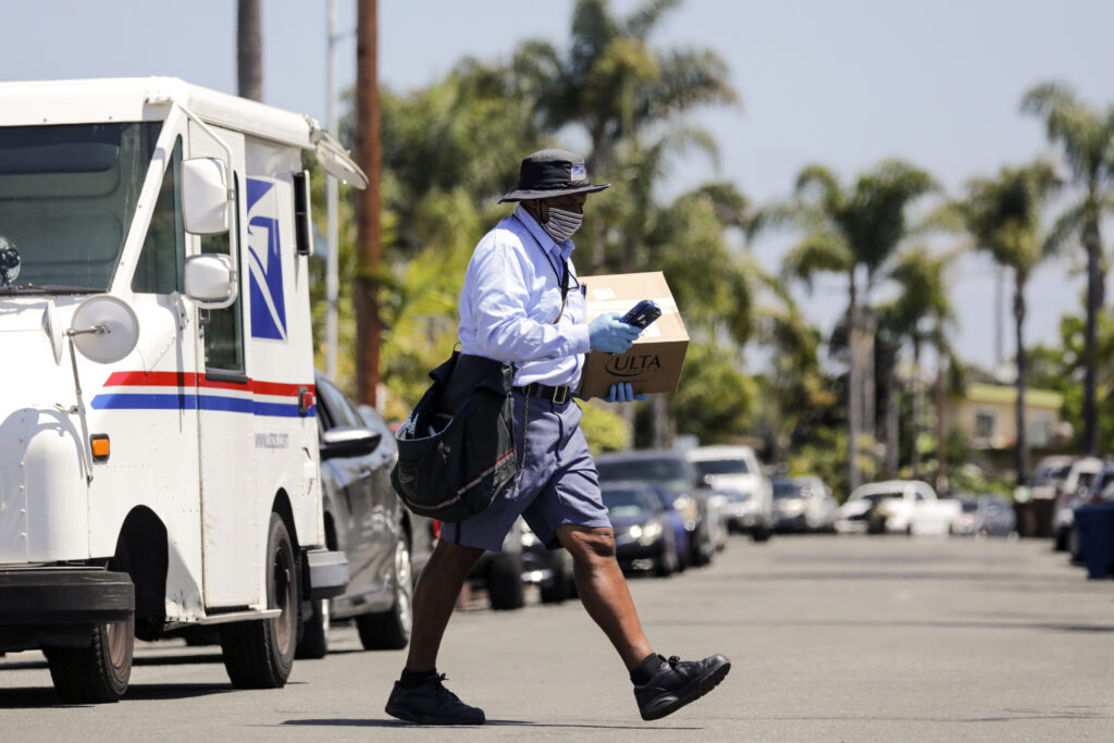 USPS mailman James Daniels carries an Ulta beauty box on his mail delivery route.